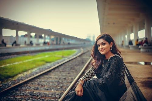 女人坐在鐵路平台上, 穿著黑色紗麗 的 免費圖庫相片