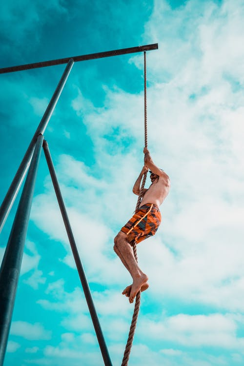 Man About to Climb Using Brown Rope