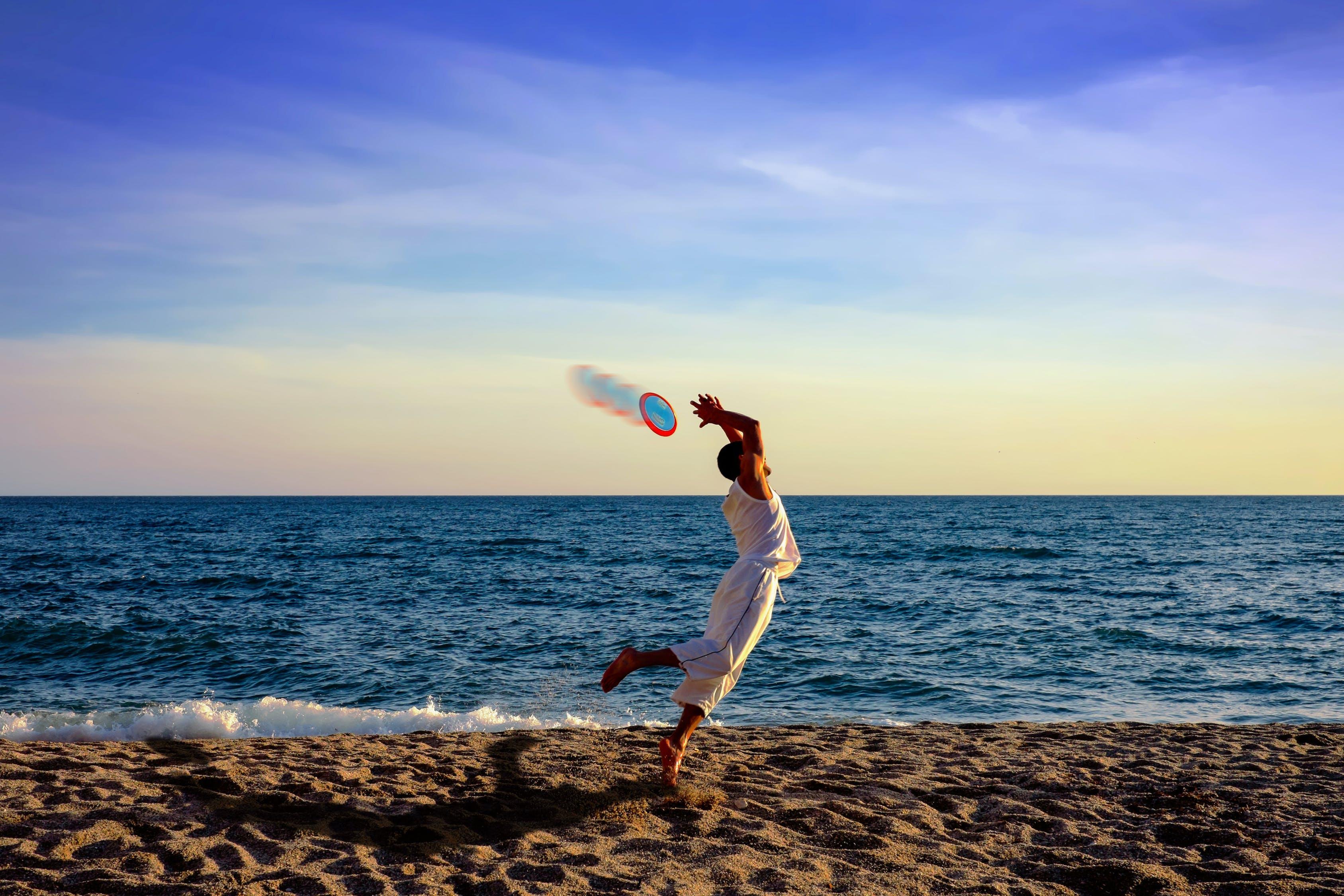 man running to catch the Frisbee near the beach
