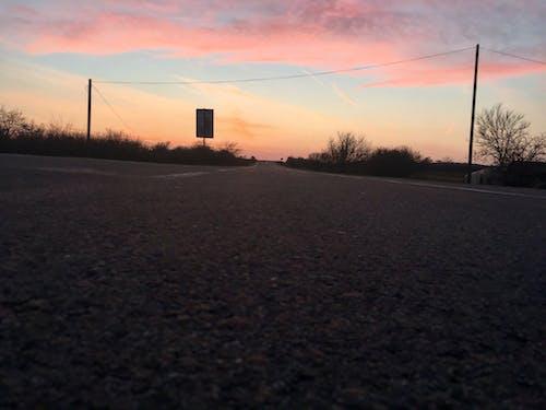 Бесплатное стоковое фото с асфальт, дорога, закат, знак