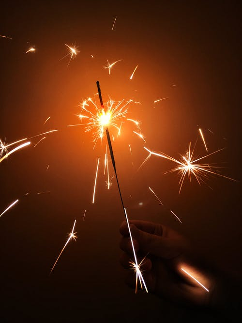 Photo of Person's Hand Holding a Sparkler
