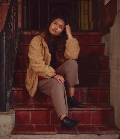 Woman in Brown Sweater and Gray Pants Sitting on Red Concrete Stairs