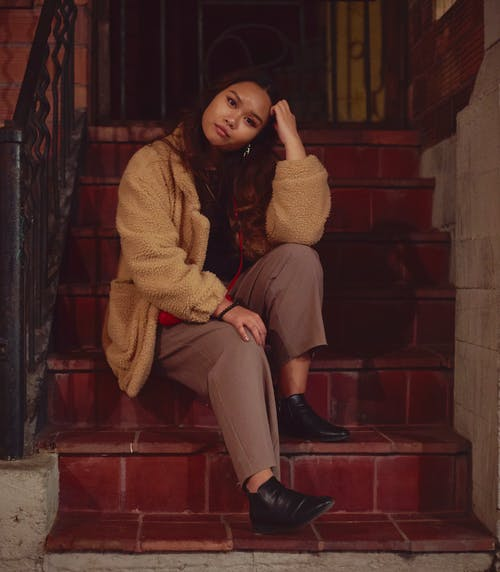 Woman in Brown Knit Sweater and Gray Pants Sitting on Red Concrete Stairs