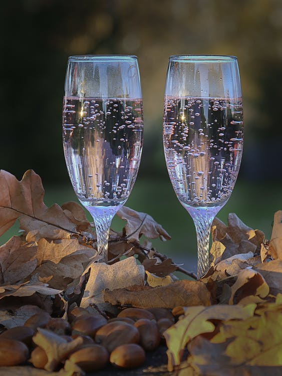 Two 3/4 Pink Liquid-filled Clear Champagne Flutes Surrounded With Dried Leaves and Brown Nuts