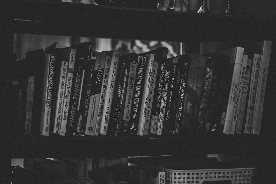 Grayscale Photography of Books Stacked in Shelf