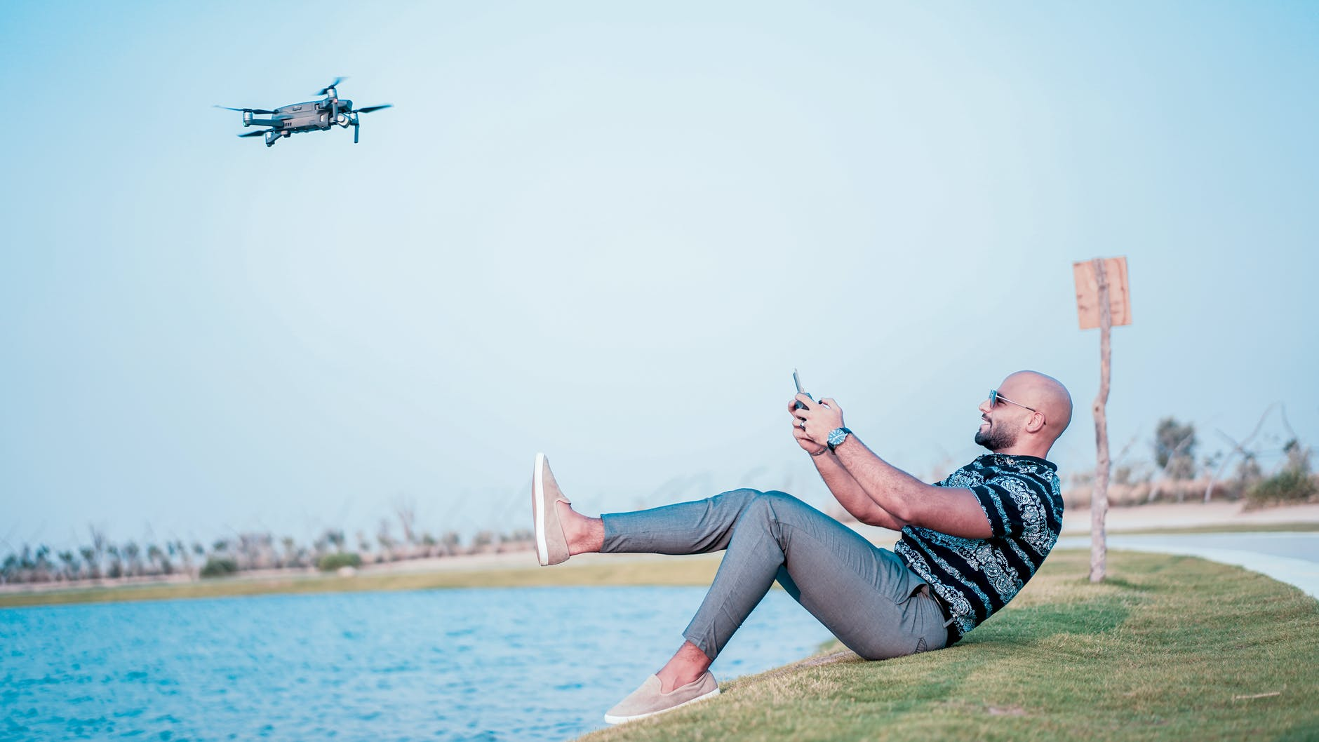 person sitting on the ground flying his drone