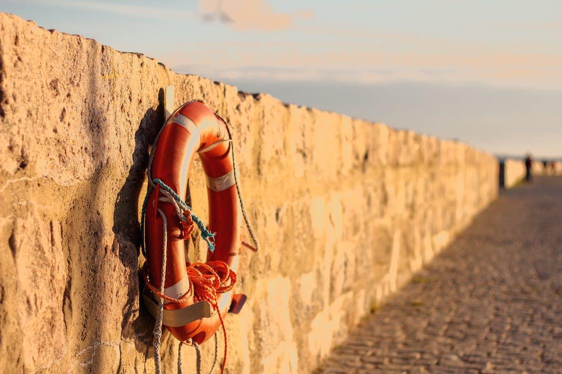 Orange Lifebuoy Hanged on Brown Wall