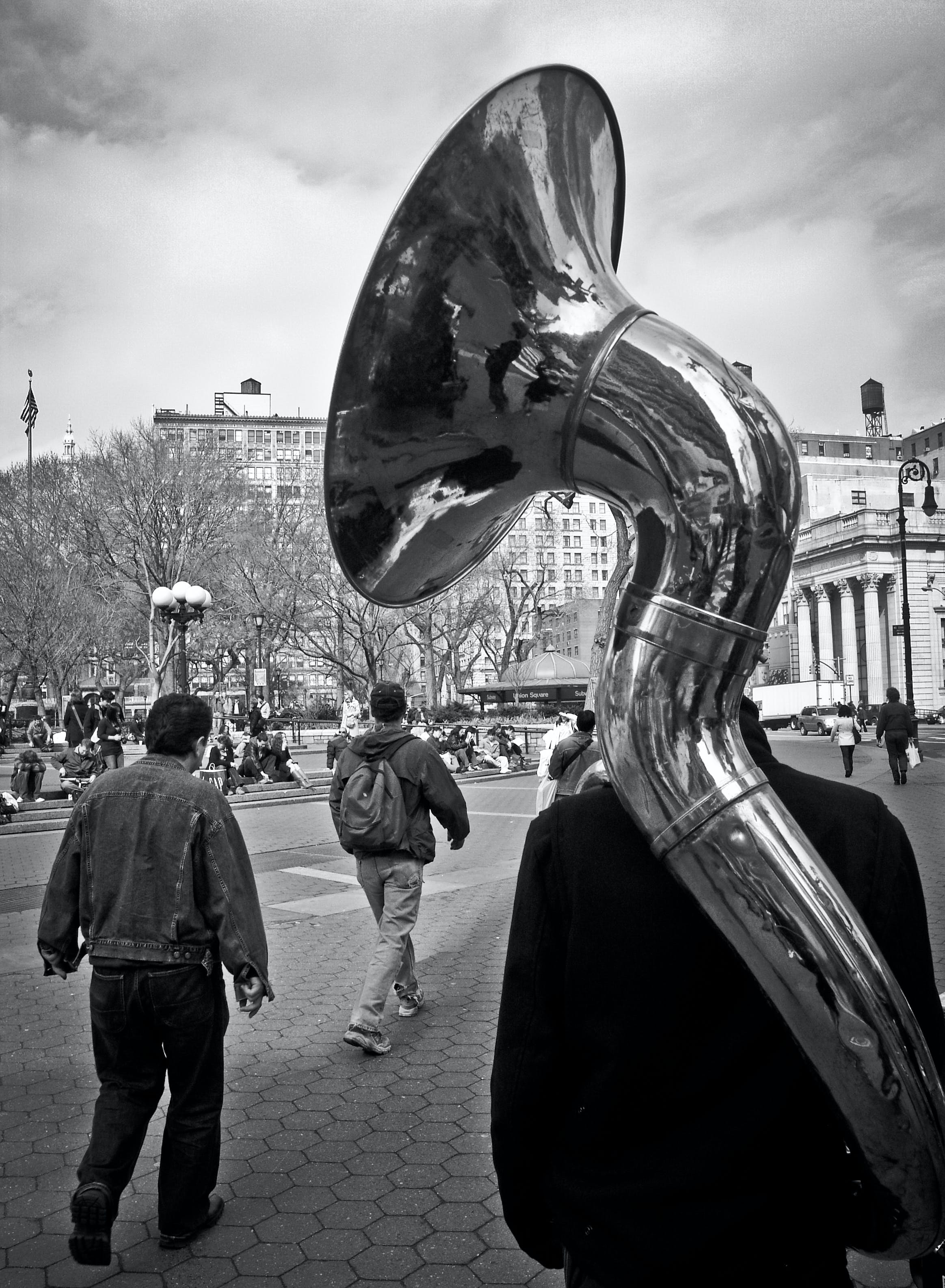 Grayscale Photo of Man Carrying Percussion Instrument