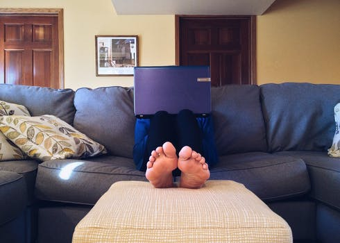 Person Sitting on Couch While Using Laptop Computer