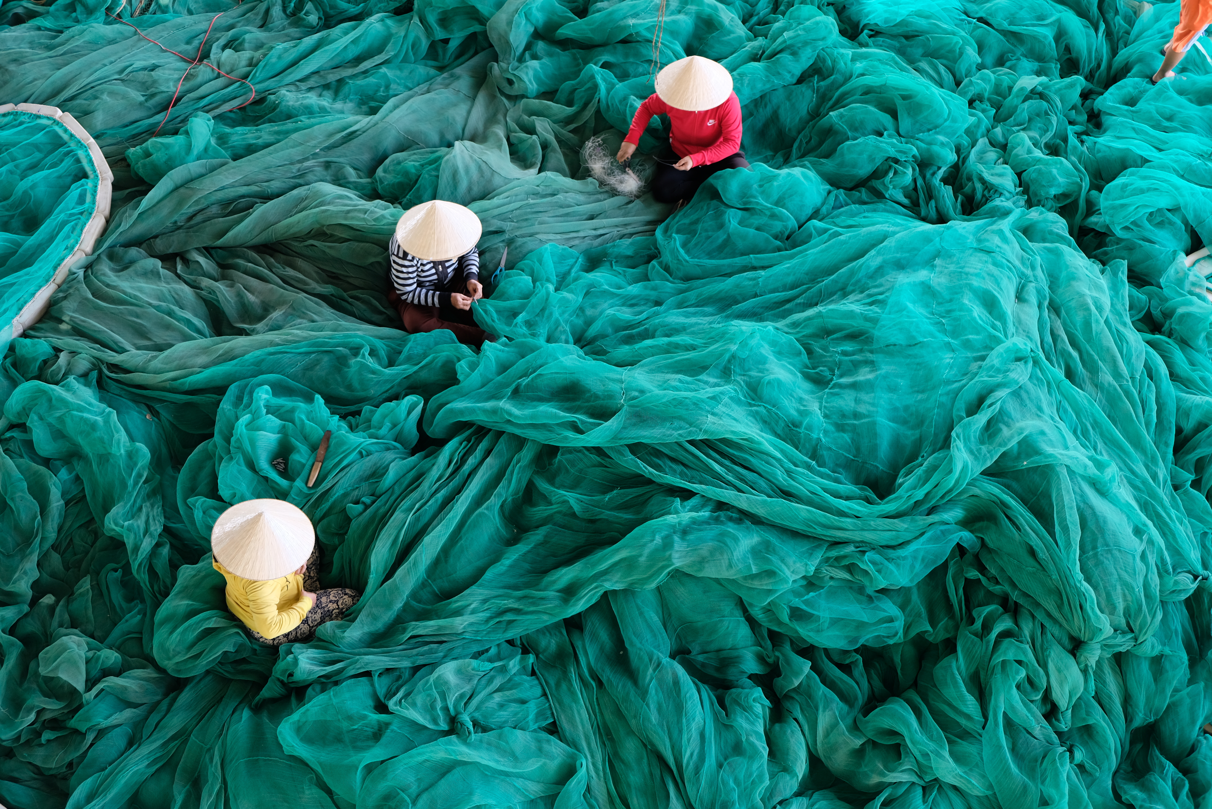 three person sitting on green large net