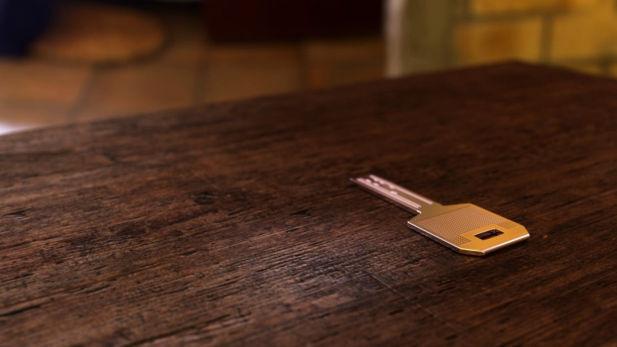 Silver Key on Brown Wooden Table
