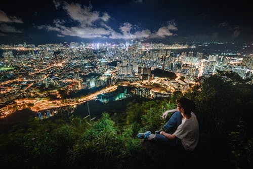 Photo of Man Sitting While Overlooking a City
