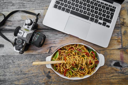 Black and Gray Dslr Camera next to a Laptop and Bowl of Noodles