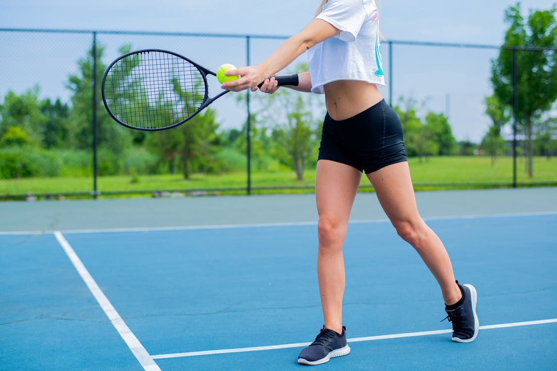 Woman Wearing Black Shorts and White Crop Top Holding Tennis Racket and Tennis Ball