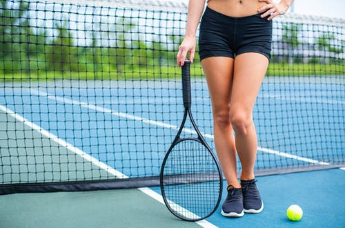 Photo of Woman Wearing Black Shorts Standing and Holding Tennis Racket