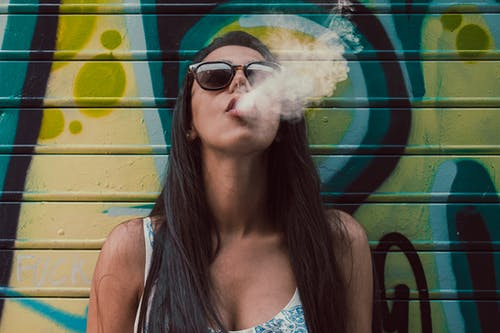 Photo of Woman Wearing Sunglasses While Smoking