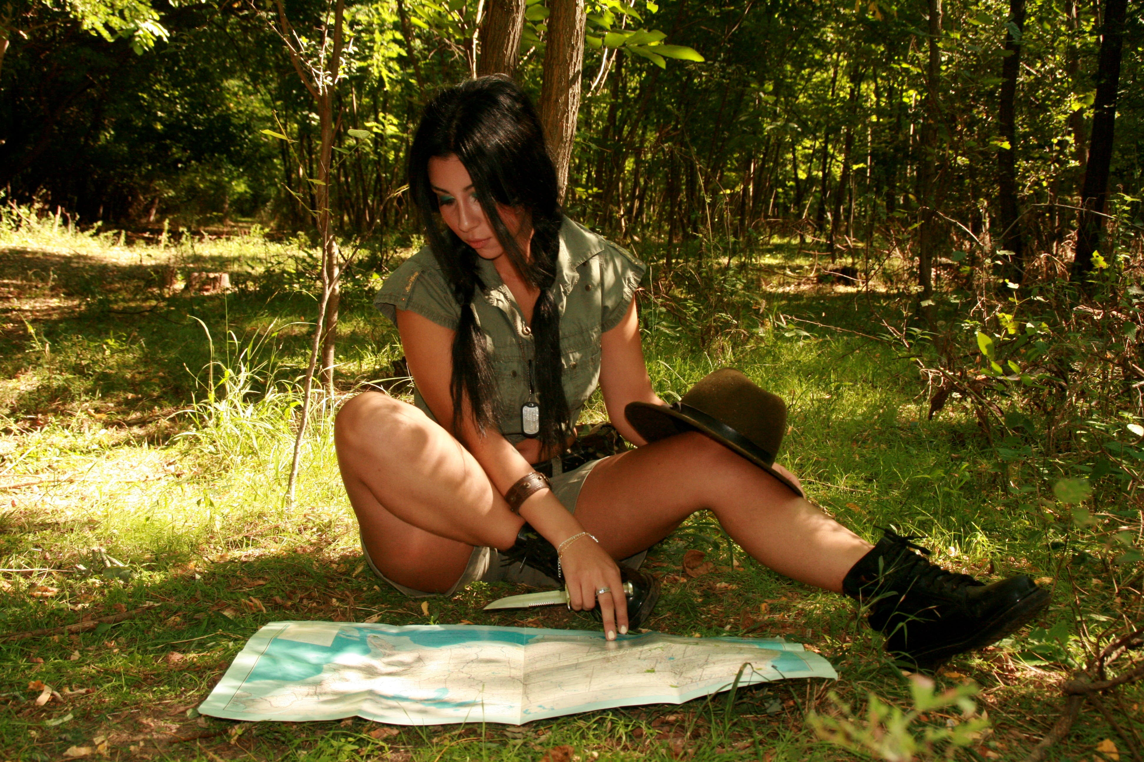 Woman Sitting on Field While Staring on Map