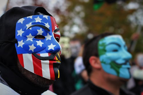 Close-Up Photo of Person Wearing Guy Fawkes Mask