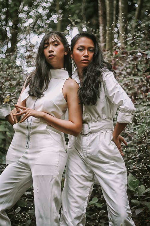 Photo of Two Women Wearing White Jumpsuit