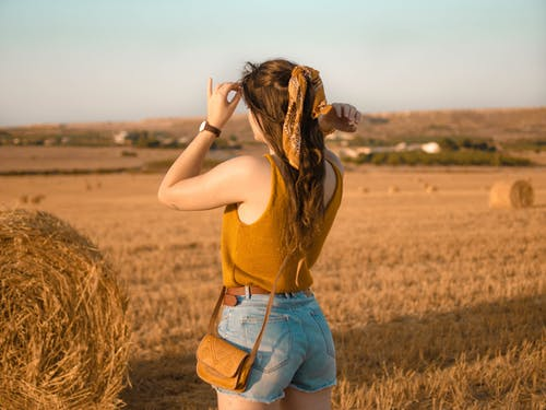 Photo of Woman Standing on Hay Field
