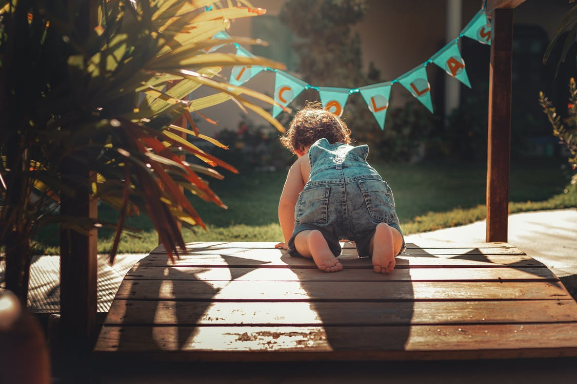 Baby Crawling on Wooden Panel