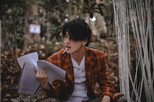 Photo of Man Smoking While Holding Papers