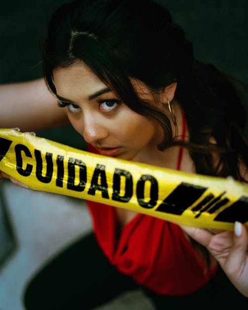 Woman Holding Black and Yellow Caution Tape