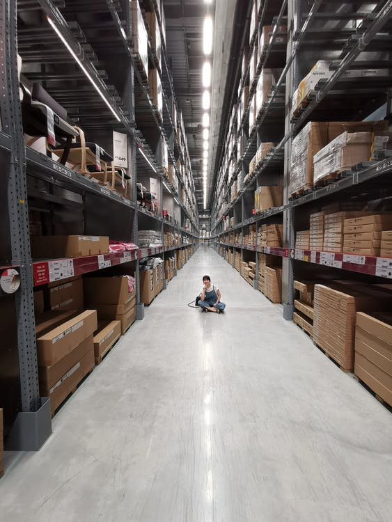Person Sitting on Ground Between Brown Cardboard Boxes