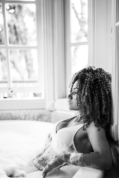 Greyscale Photo of Woman in Bath Tub
