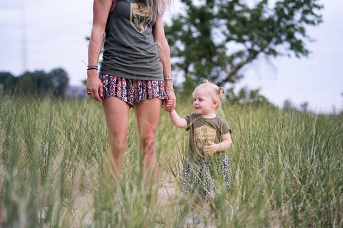 Woman Standing and Holding Hand of Baby Near Green Field