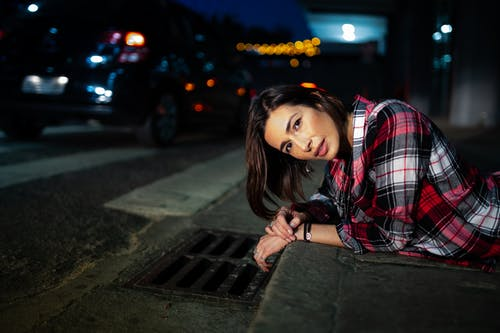 Photo of Woman in Plaid Shirt Lying Down on Curb at Night