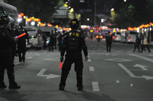 Police Standing on Gray Asphalt during Nighttime