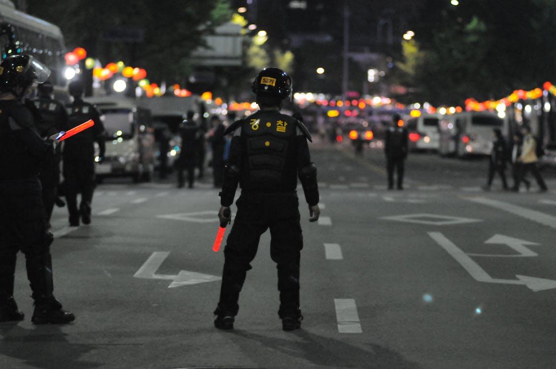 Police Standing on Gray Asphalt during Nighttime