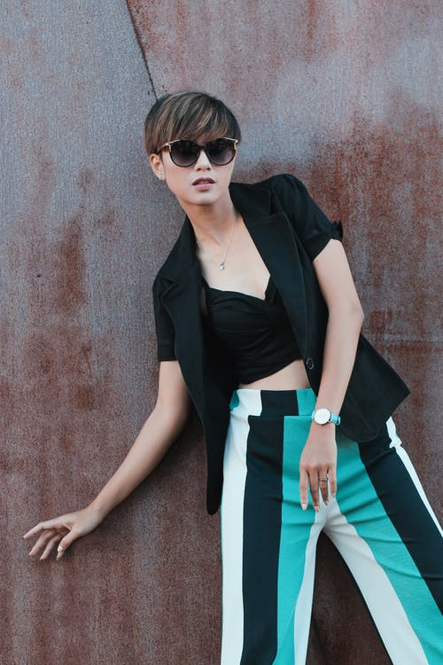 Standing Woman Wearing Black Blazer and White and Teal Striped Pants