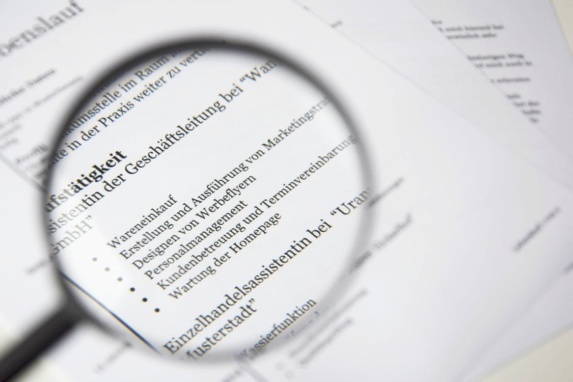 Magnifying Glass Beside White Printer Paper