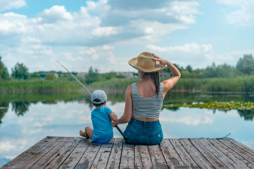 Woman and Boy Sitting on Dock Holding Fishing Rod