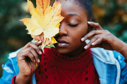Selective Focus Photography of Woman Covering Face With Brown Leaf