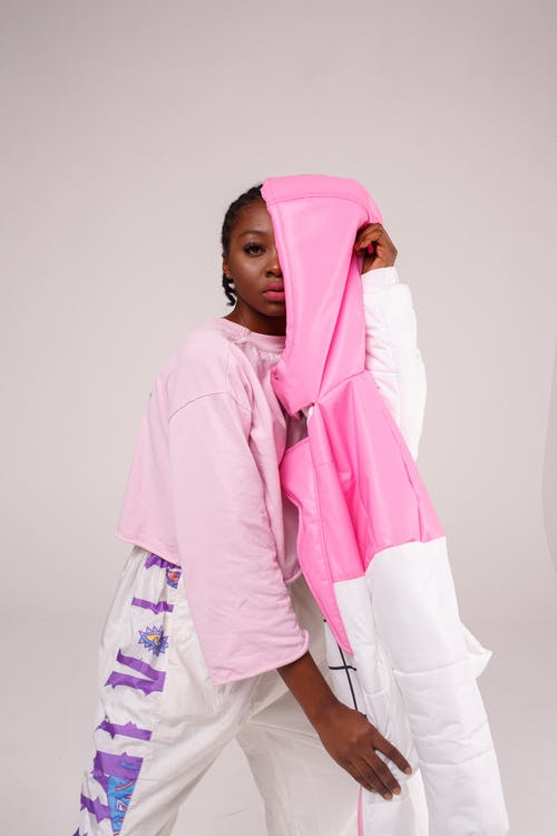 Woman Standing and Covering Half Face Using White and Pink Jacket