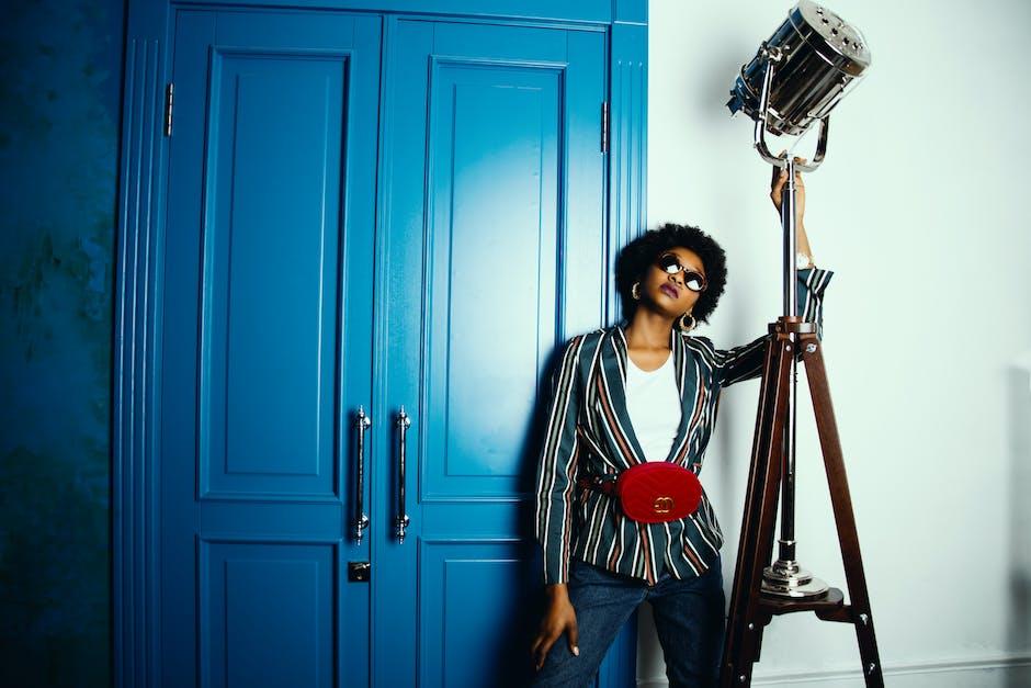 Woman in striped blazer standing near blue wooden door