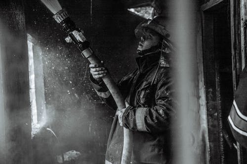 Grayscale Photography of a Fireman Holding a Hose