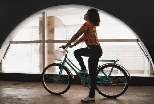 Woman Sitting on Bicycle Inside Building by the Arch Window
