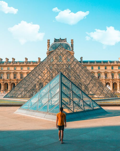Man Standing in Front of Louvre Museum of Paris