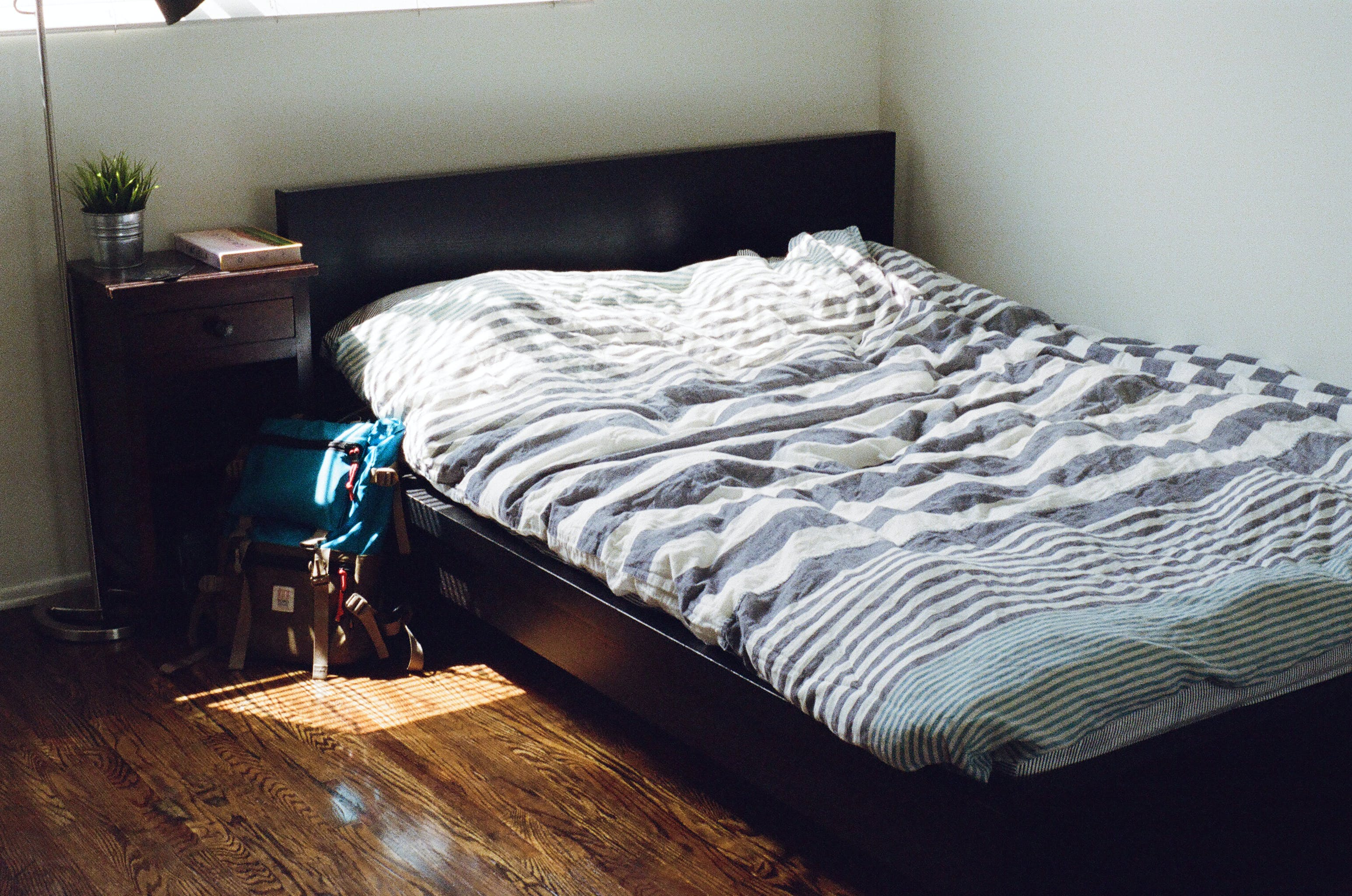 Black Wooden Bed Framed and White and Gray Striped Bedspread