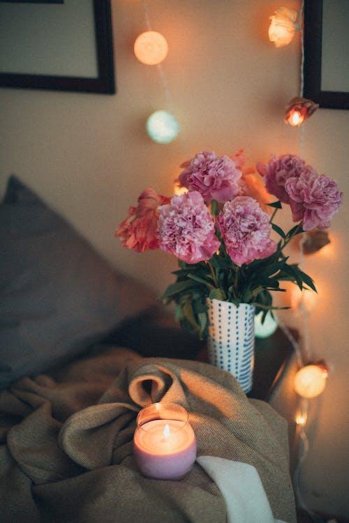 lọ hoa cẩm chướng màu hồng bên cạnh nến thơm và giường