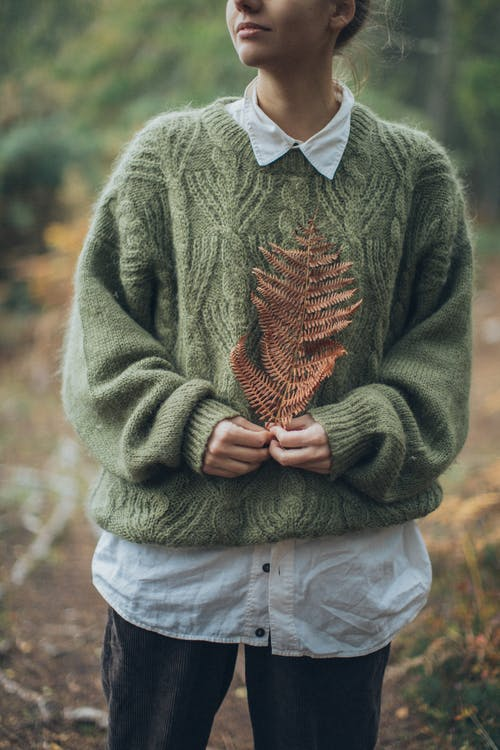 Woman Wearing Green Sweater Holding Dried Pine Leaf