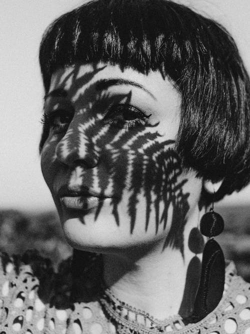 Woman With Shadow Of Fern Leaves On Face