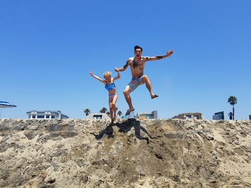 Photo of Man And Girl Jumping On Sand