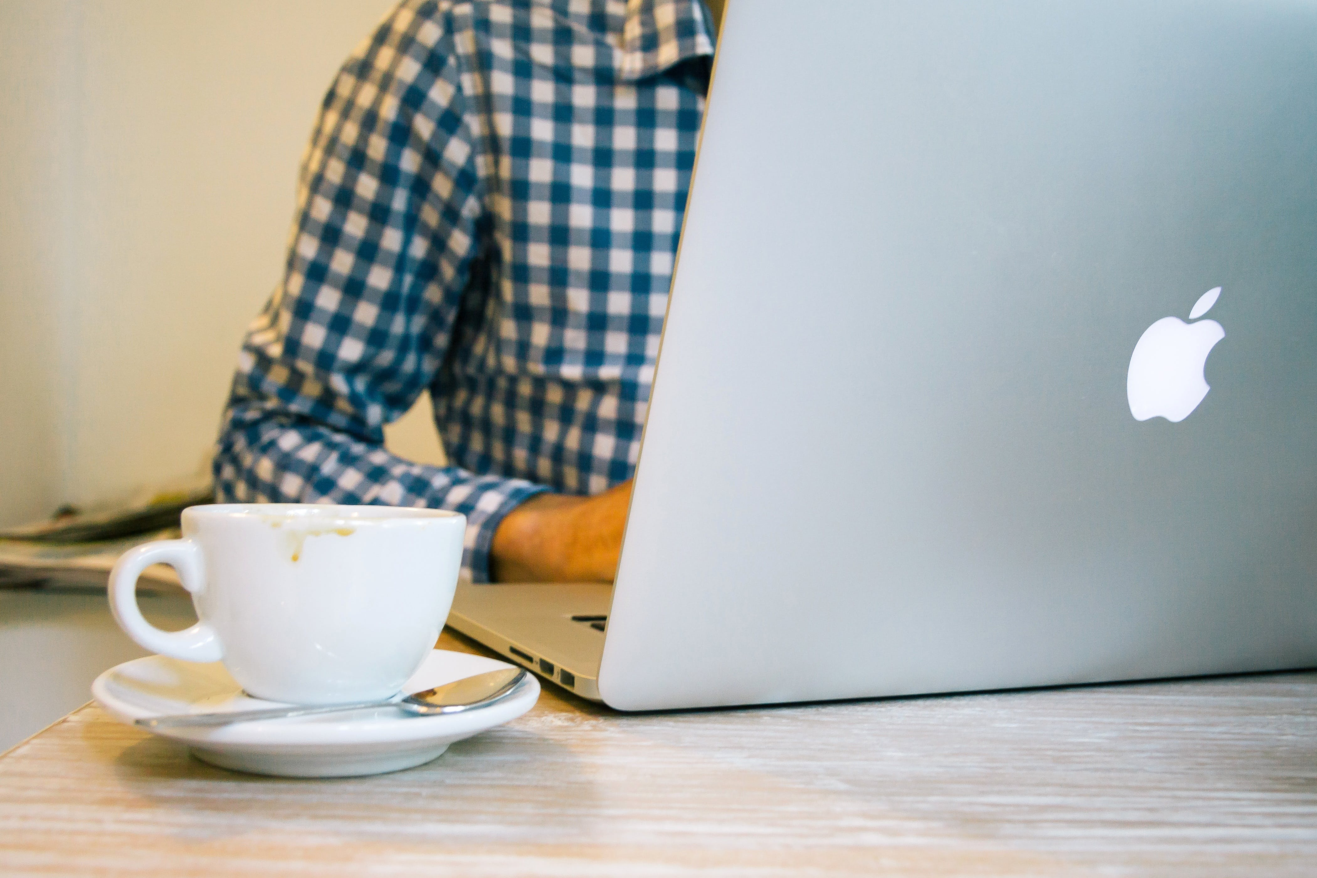 White Ceramic Teacup Beside Silver Macbook on Table