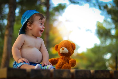 Smiling Toddler Beside Orange Bear Plush Toy