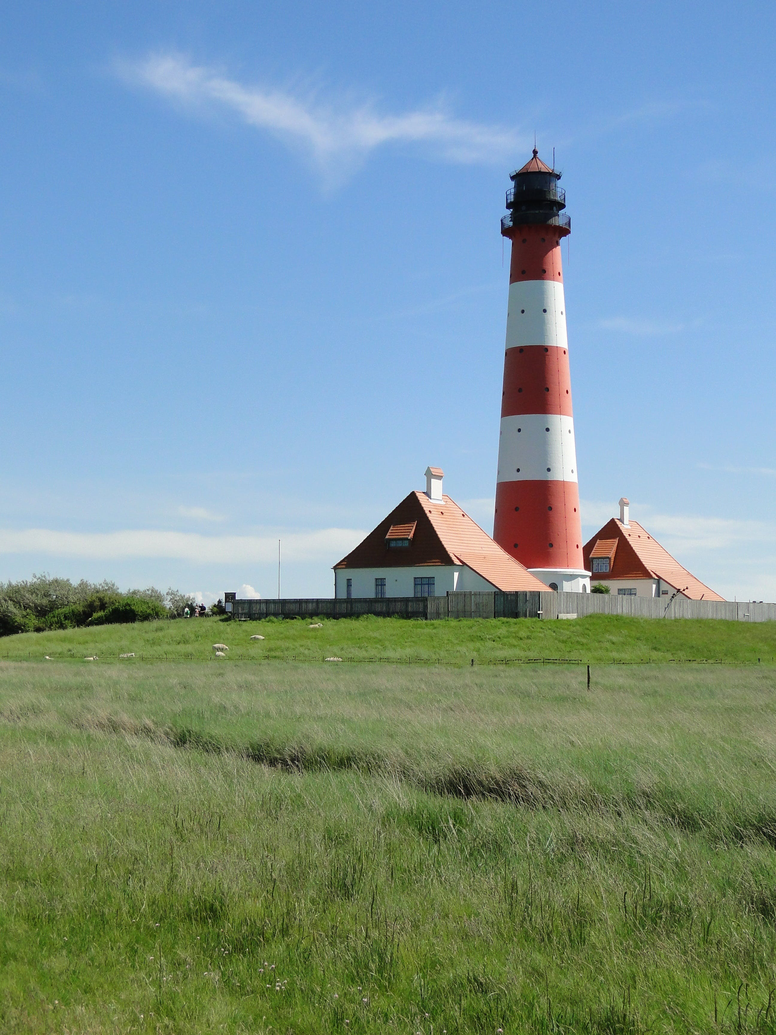 White and Red Lighthouse Near Grass